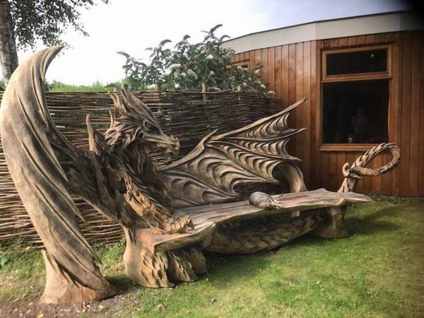 Un artista estonio talla con una motosierra un dragón en un banco