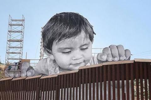 Un niño gigante aparece en el muro entre México y EE.UU